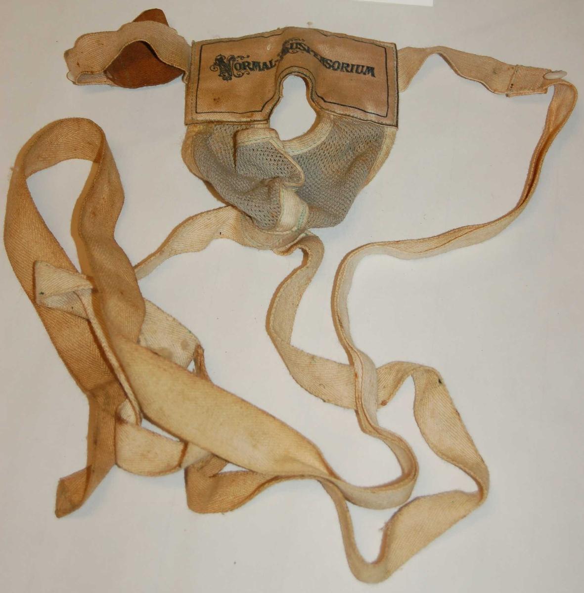 Stoffpose som omslutter pungen med åpning foran til penis. Posen er festet til tøystropper som festes omkring livet for å halde pungen oppe.