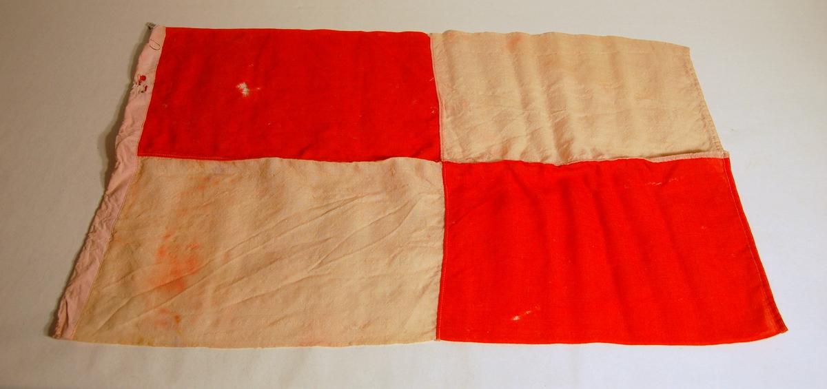 """Gjenstanden er et signalflagg i fargene Rød, Kvit, og som symboliserer bokstaven """"U""""."""