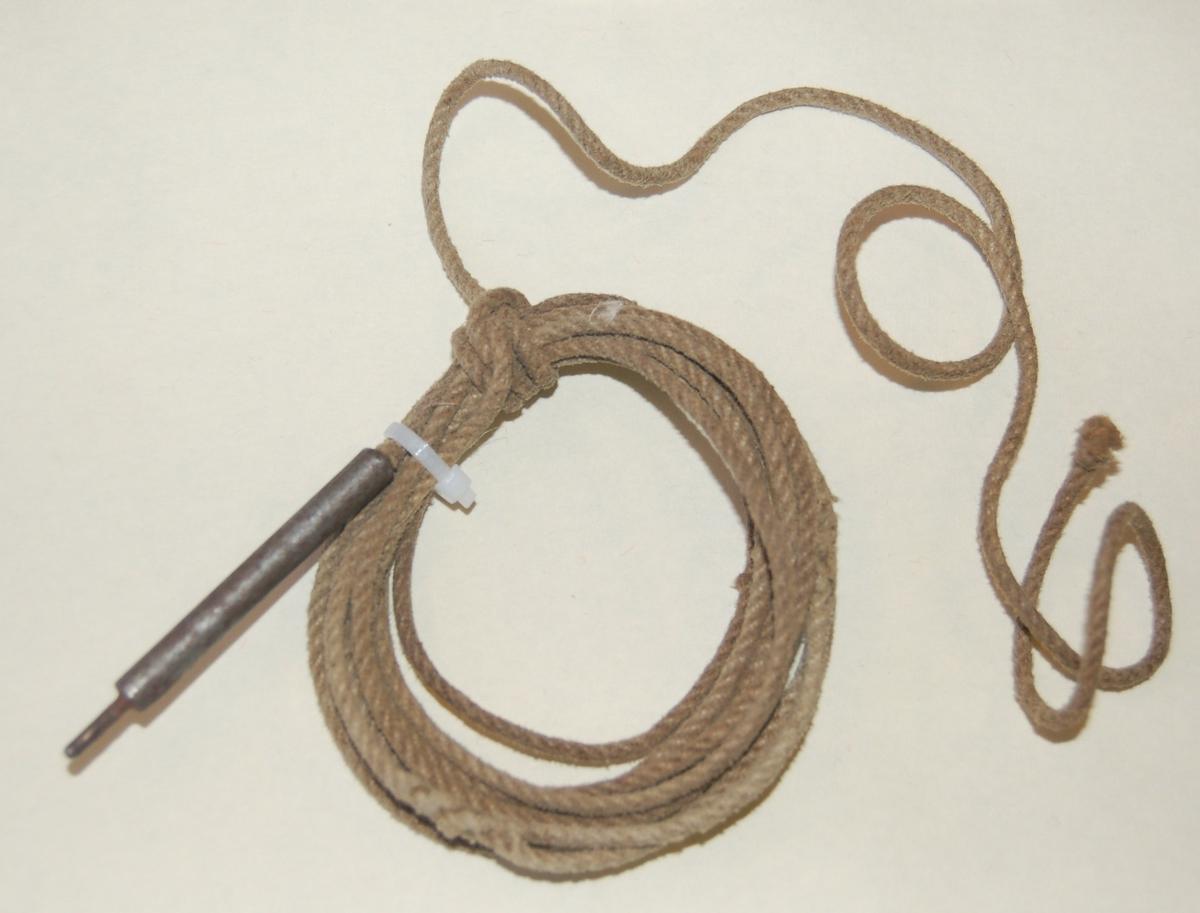 Gjenstanden består av en tynn tauline. I enden på linen er det festet eit 6 cm. jernlodd,  for lettere å træ linen gjennom børseløpet. 116 cm. frå loddet er der spleiset på en løkke til festing av pussefillen.