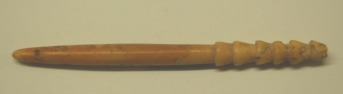 Pilspissen er sylindrisk i formen, og mest sannsynlig bearbeidt ut fra en kvalrosstann. Spiss i en ende, og med mothaker til innfesting til pilemnet i den andre enden.