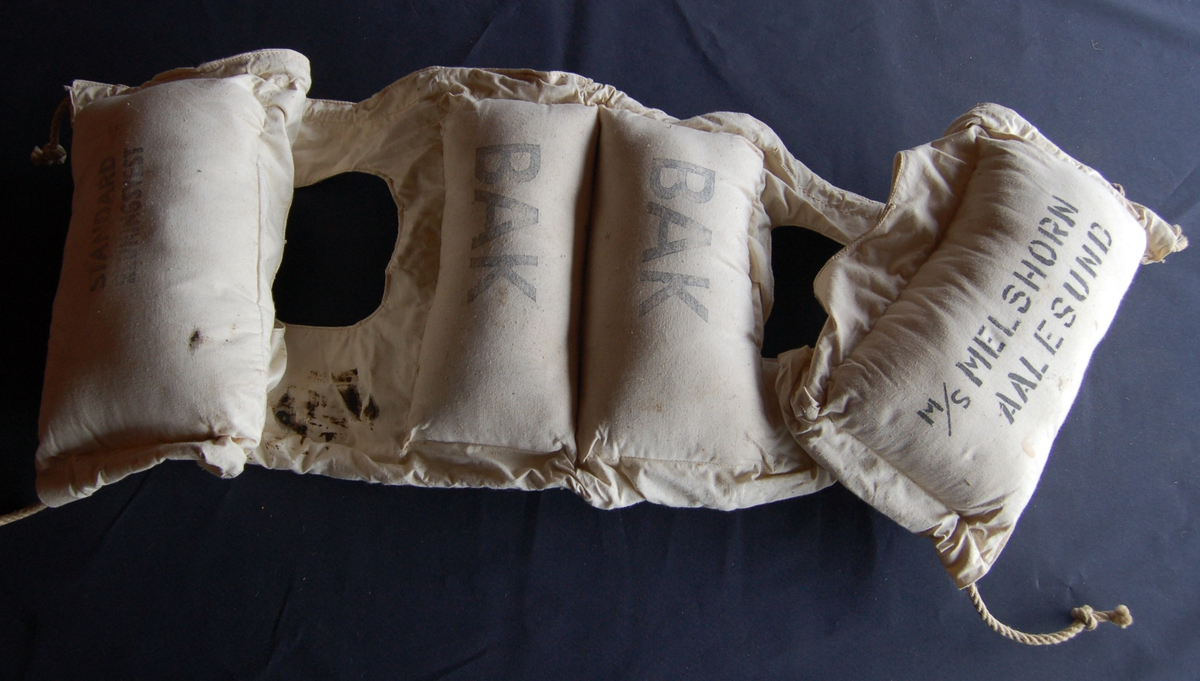 Vesten er av seildukslignande stoff, der flyteposane er fylt med kapok, ein slags vannavstøtende mjuk filt el.l. Mellom posane er der to hull til å træ armane gjennom, og lisser til å knyte den fast med foran på brystet.