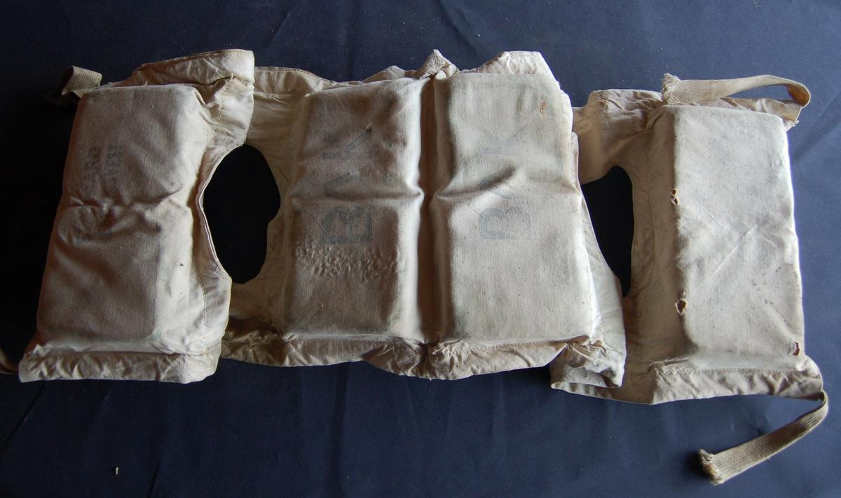 Vesten er av seildukslignande stoff, der flyteposane er fylt med kork.  Mellom posane er der to hull til å træ armane gjennom, og lisser til å knyte den fast med foran på brystet.