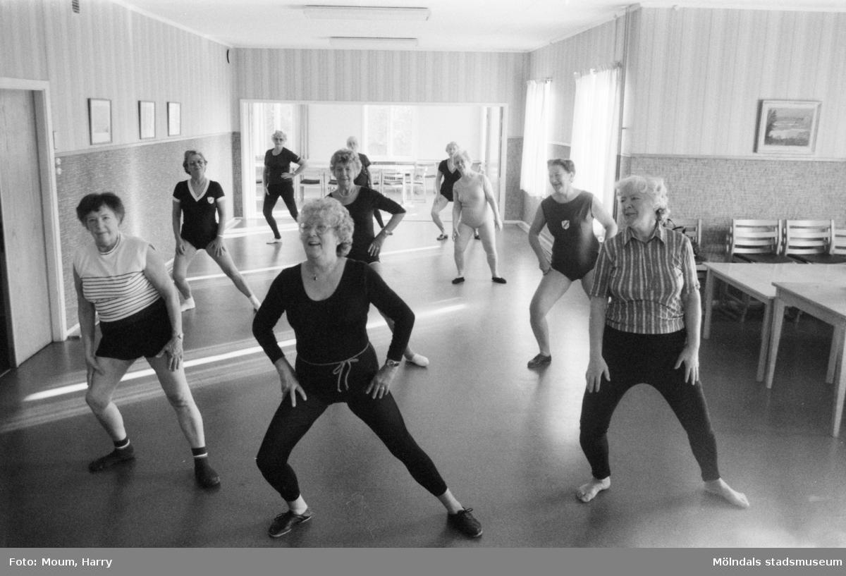"""Mölndals-korpen anordnar aktiviteter för äldre i Mölndal, år 1984. Gymnastik. """"Eivor Bjerrhede visar hur rörelsen utförs."""" Kortet taget i Kållereds kommunalhus, rivet i början av 1990-talet. Adress: Streteredsv. 3.  För mer information om bilden se under tilläggsinformation."""