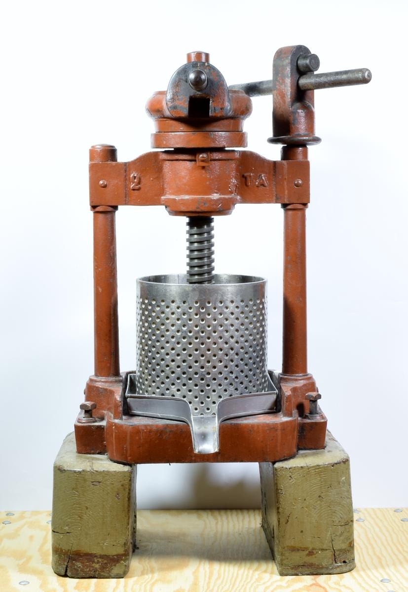 Urtepresse i delvis rødmalt metall. Pressen hviler på to massive treføtter.   I selve pressen ligger det fem metallstenger på ca. 10 x 2,5 cm.