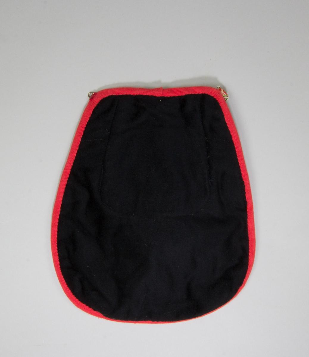 Kjolsäck till dräkt för kvinna från Leksands socken, Dalarna. Modell med u-formad öppning. Tillverkad av svart ylletyg, kläde, med applikationer av kläde i gult, grönt och rött, fastsydda med läggsöm. Centralt placerad hjärtblomma med slingor och mindre hjärtan på sidorna, trekanter längs kanterna. Broderi utfört med bomullsgarn i flera färger: flätsöm, stjälksöm, sticksöm. Framstycket fodrat med vitt bomullstyg, fabriksvävt, tuskaft. Kantad runtom med rött diagonalvävt ylleband. Bakstycke av svart kläde, med grönt kläde monterat i öppningen. Midjeband fabriksvävt, av bomull med mönster i rött på vit botten, med hake och hyska.