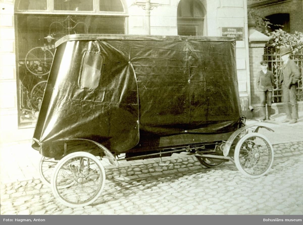 """Bil med kapell parkerad på en kullerstensgata. Cykelaffär med text på glasrutan """"Velocipedförsäljnings Aktiebolaget"""""""