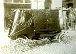 Bil med kapell parkerad på en kullerstensgata. Cykelaffär me