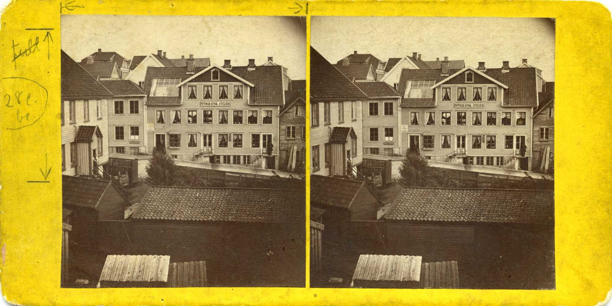 """Huset til kjøpmann Peder Amlie med fotografiatelier i loftsetasjen. Huset er et to og en halv etasjes bygg, med en bred ark i takflaten ut mot gaten. Arken gir plass til hele fire vinduer og et loftsvindu over. Et skilt med teksten: Fotografisk Atelier, danner skillet mot andre etasje som har åtte vinduer på rekke. Første etg. har tre innganger. Over den venstre står :""""P. Amlie"""".  Torggt. i forgrunnen. Strandgt. til venstre i bildet."""