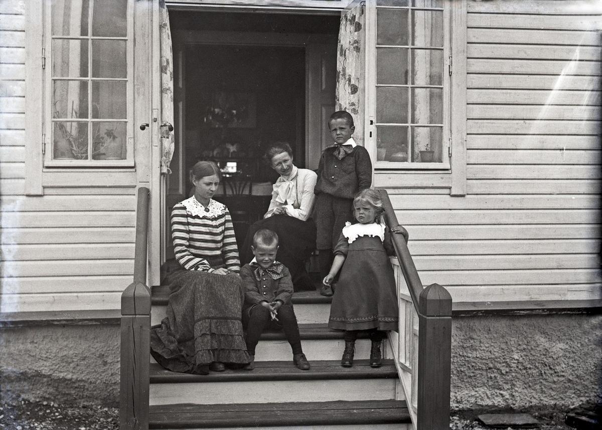 Eksteriør - Gruppebilde. To kvinner og tre barn på trappen foran et bolighus