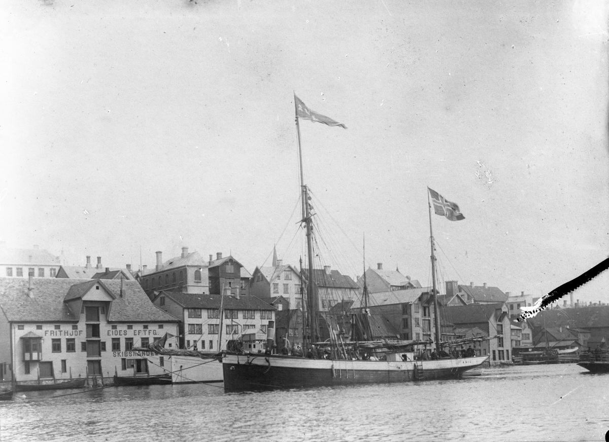 """Sluppen """"Ægil"""" i Smedasundet, Haugesund. """"Ægil"""" har flagg i toppen av begge mastene, men seilene er tatt ned."""