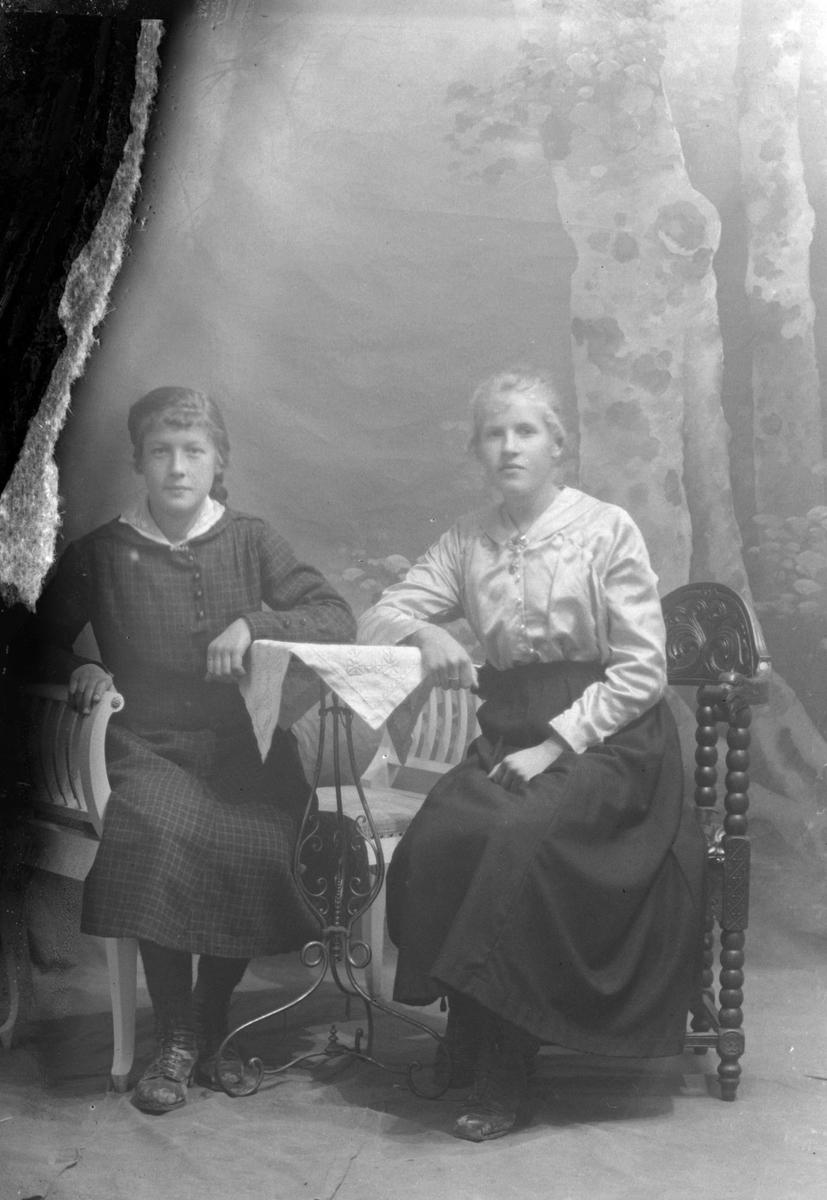 Studioportrett av to kvinner sittende ved et bord.
