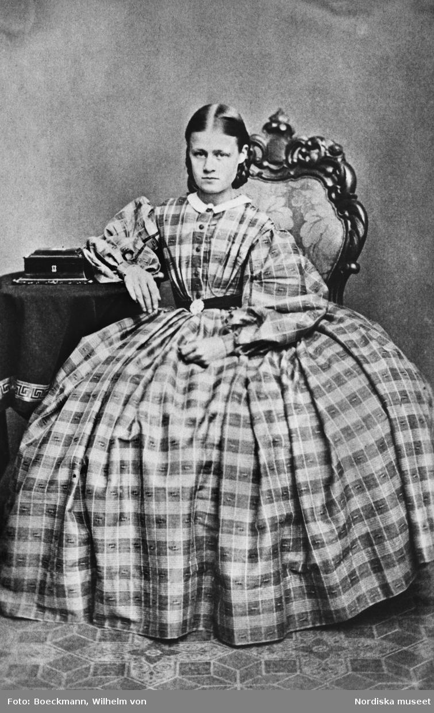 Porträtt av ung kvinna, Anna Carolina Östrand (född 1845) sittande vid bord iklädd rutig klänning, krinolin, med puffärmar och vit krage.
