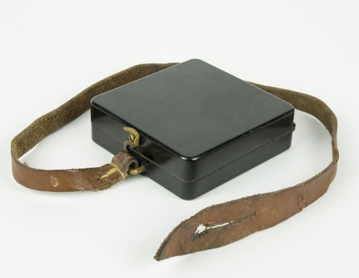 Kompass med hopfällbart lock i bakelit. Kompassen är fäst i en läderrem.