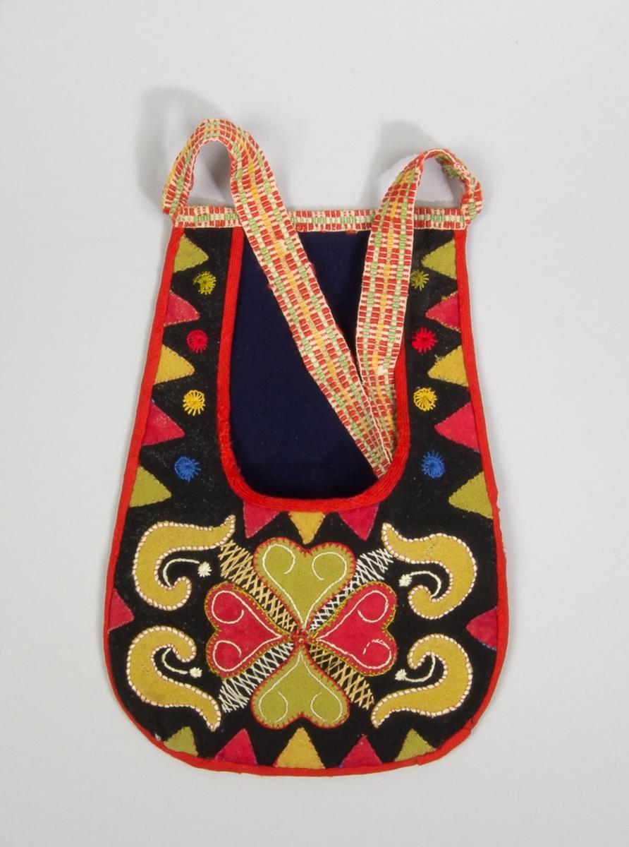 Kjolsäck till dräkt för kvinna från Leksands socken, Dalarna. Modell med u-formad öppning. Framstycke av svart ylletyg, kläde, med applikationer av kläde i gröngult och gulgrönt, fastsydda med läggsöm, langettsöm och kaststygn. Motiv: centralt placerad hjärtblomma med slingor och trekanter på sidorna, broderade rundlar. Broderi utfört med glansigt bomullsgarn i flera färger: flätsöm, stjälksöm och langettsöm. Framstycket fodrat med vitt bomullstyg. Kantat runtom med rött diagonalvävt ylleband. Bakstycke av svart kläde. Midjeband handvävt, med plockat mönster av rött, grönt och gult ullgarn på vit botten.