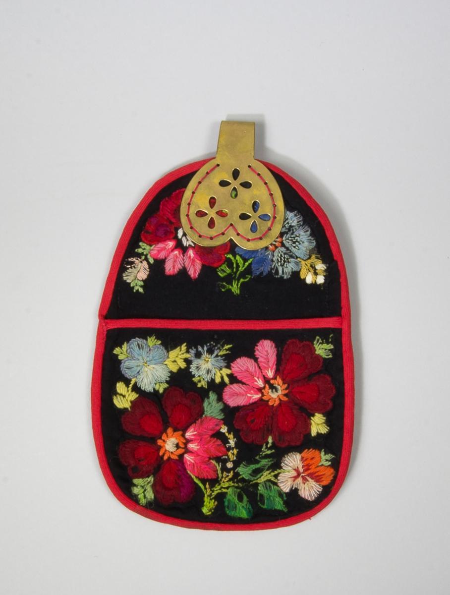 """Kjolsäck till dräkt för kvinna från Floda socken, Dalarna. Modell med avskuret framstycke. Tillverkad av svart ylletyg, gabardin, med broderi, """"påsöm"""", utfört med ull- och bomullsgarner i många färger. Motiv: blommor och blad, sydda med plattsöm, sticksöm och knutar. Broderiet har hämtats från en äldre kjolsäck, klippts ut och monterats på denna. Kantad runtom med rött diagonalvävt ylleband. Framstycket fodrat med grått bomullstyg. Bakstycke av svart yllegaberdin, med mellanlägg av svart maskinstickat bomullstyg. Beslag med fast hake tillverkad av mässingsplåt, med stansad dekor på framsidan. Beslagtillverkarens namn stämplat på baksidan: A. FROST ÄLVDALEN."""