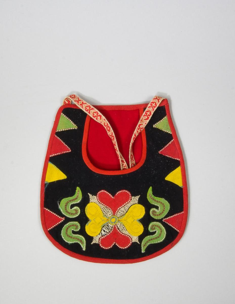 Kjolsäck till dräkt för kvinna från Leksands socken, Dalarna. Modell med u-formad öppning. Framstycke av svart ylletyg, med applikationer av kläde i rött, gult och grönt, fastsydda med läggsöm. Motiv: centralt placerad hjärtblomma med slingor och trekanter på sidorna. Broderi utfört med ull- och silkegarn i flera färger: flätsöm och langett. Kantad runtom med rött diagonalvävt ylleband. Framstycket fodrat med gult bomullstyg, tuskaft, fabriksvävt. Bakstycke av svart kläde, med rött ylletyg i öppningen. Midjeband handvävt, med plockat mönster i glansigt rött garn på vit botten. Broderierna på de gula hjärtana helt bortnötta.