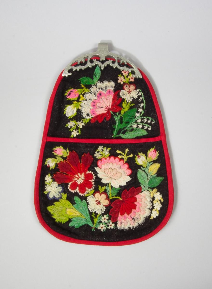"""Kjolsäck till dräkt för kvinna från Floda socken, Dalarna. Modell med avskuret framstycke. Tillverkad av troligen handvävt halvylletyg i tuskaft, med brun bomullsvarp och svart ullinslag. Broderi, """"påsöm"""", utförd med ullgarn i många färger, samt lite silkegarn. Motiv : blommor och blad, sytt med plattsöm, sticksöm och knutar. Foder av ett grått och ett brunt bomullstyg. Kantat runtom med rött diagonalvävt ylleband. Bakstycke av brunt bomullstyg. Beslag med fast hake, gjuten och genombruten, med stämplad dekor. Beslaget är av stål men har ett ytskick av tenn på framsidan."""