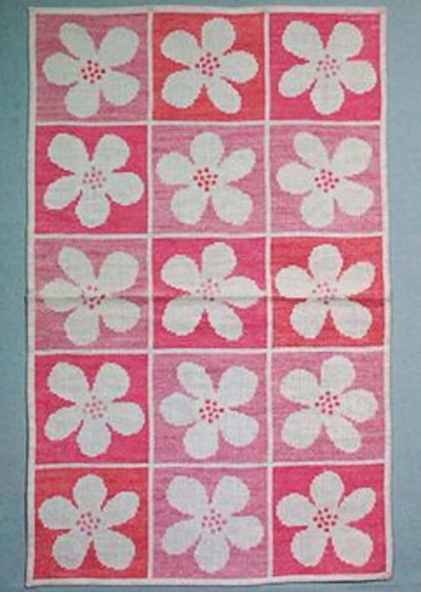 Använda som broderimodeller i hemslöjdsbutiken. Raine har även formgivit en ljusstake med samma namn och form som blomman i broderiet. Broderi med 2 x 2 blommor är 263 x 268 mm och med 3 x 5 blommor är 410 x 680. Finns i färgställningarna rosa, gult, blått, vitt.