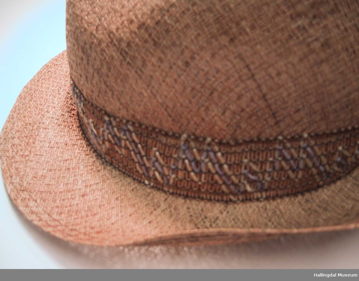 Hattebånd i siksak-mønster i hvitt og lyseblått på lysbrun bunn.