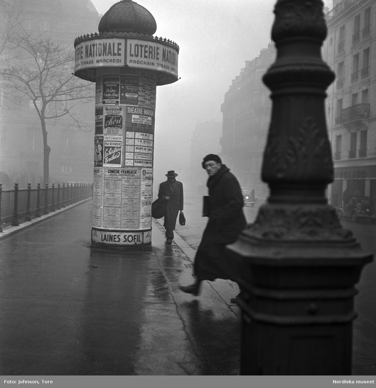 Fotgängare på en gata i Paris, annonspelare i bakgrunden.
