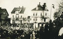 Folkemengde foran festpyntede hus. Musikere på scene pyntet