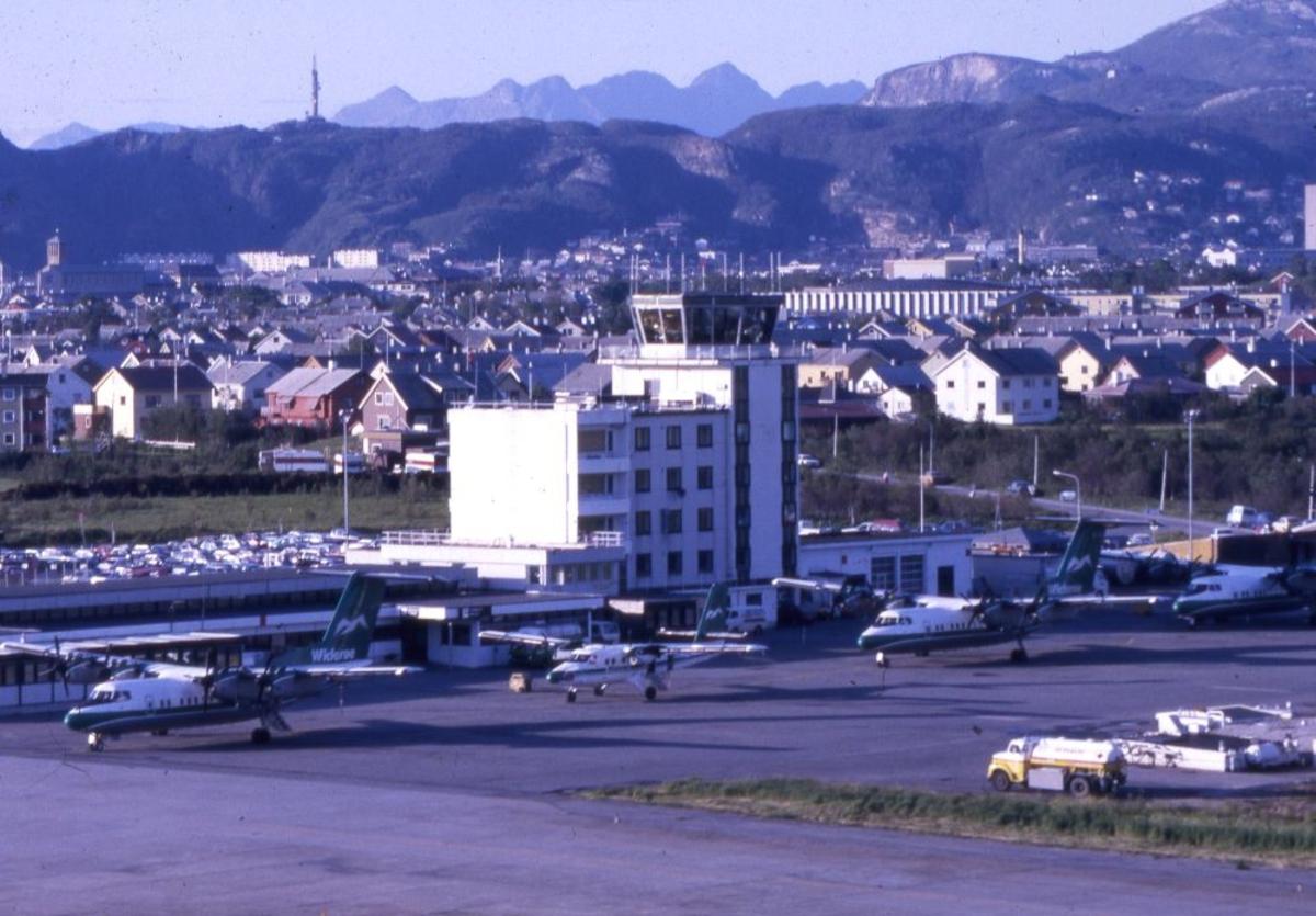 Flyplass/lufthavn. Flytårn/kontrolltårn med byen i bakgrunnen. Flere fly fra Widerøe parkert på tarmac.