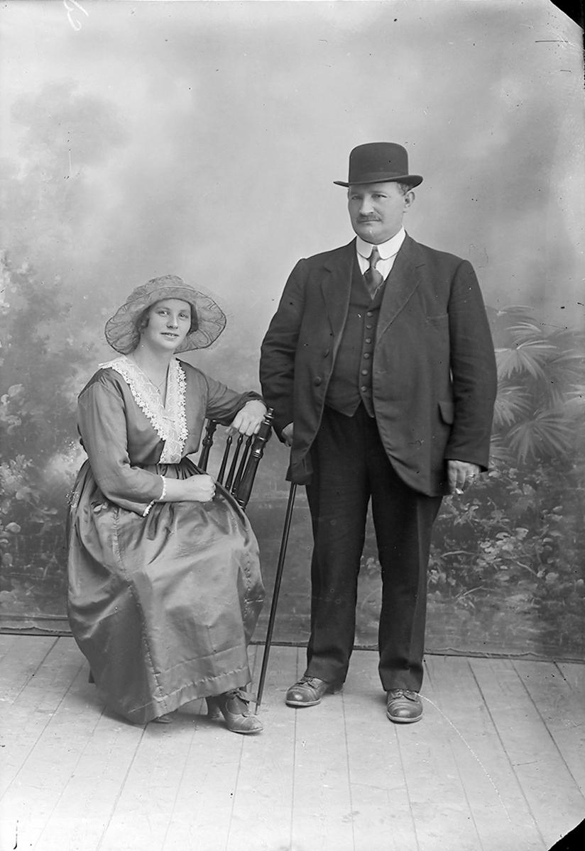 Portrett. En kvinne som sitter på en stol og en mann som står ved siden av. Kvinnen har på seg en kjole og en hatt på hodet. Mannen har dress og slips, med en hatt på hodet. I den ene hånden holder han en spaserstokk.Bildet er tatt på Inndyr.