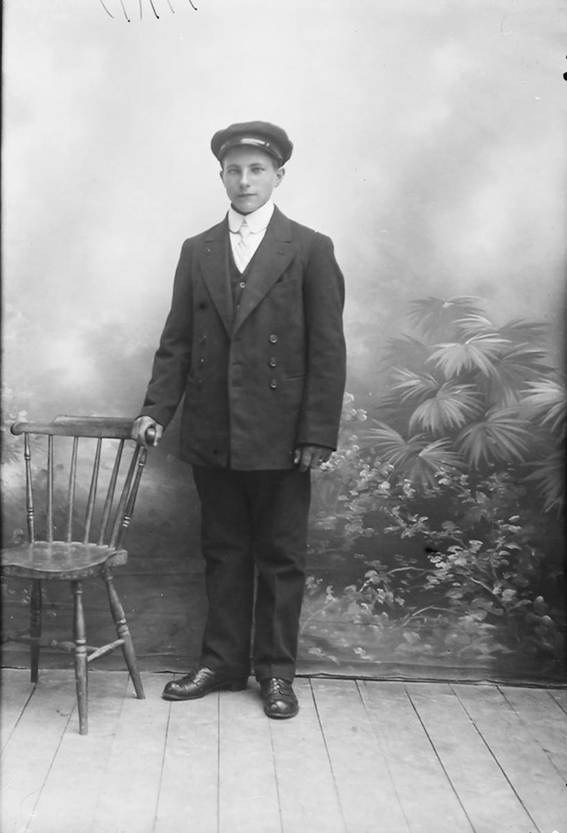 Portrett. Ung mann stående ved en stol iført en mørk dress. Konfirmant. Gildeskål. 1916.