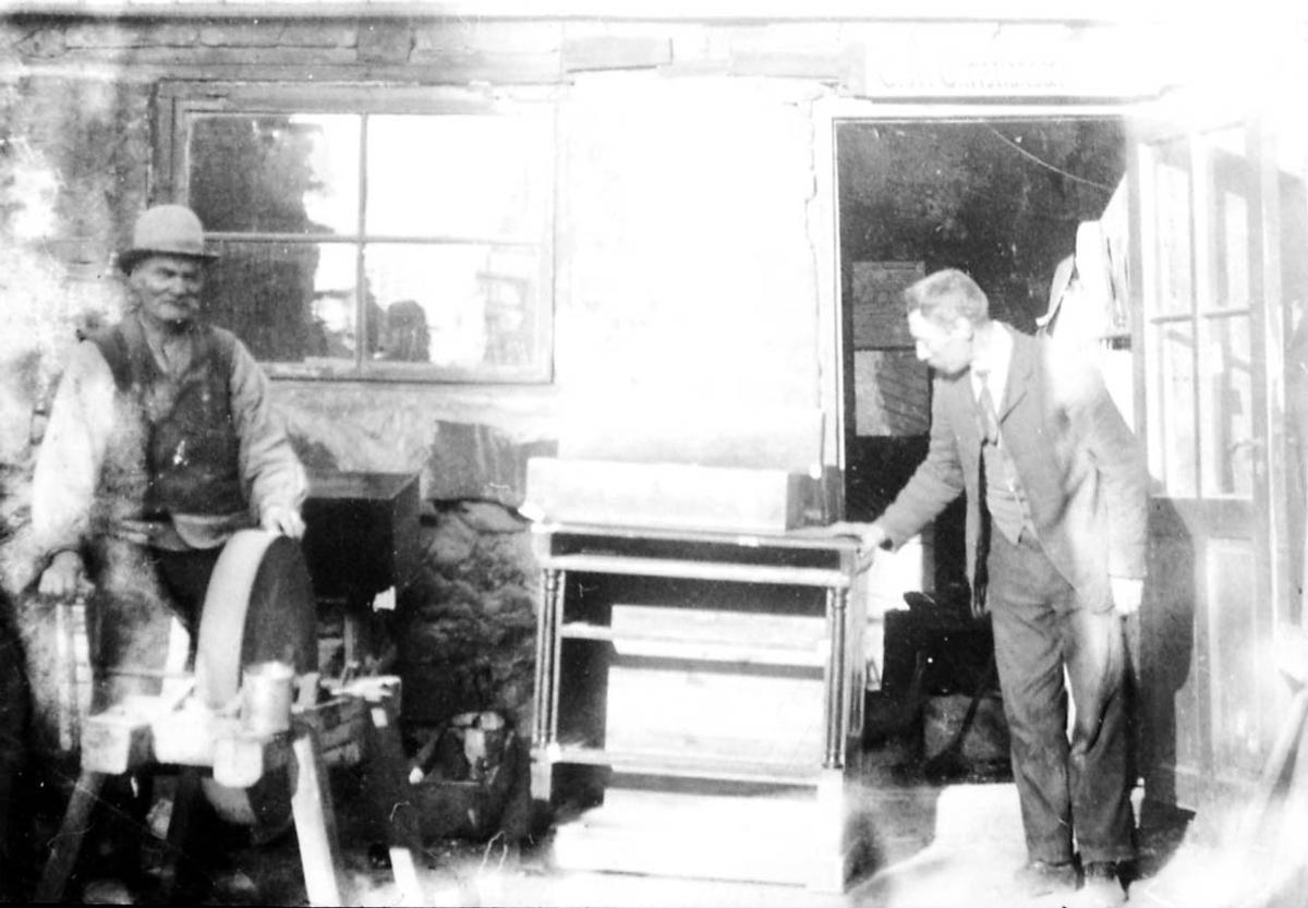 Gruppebilde. 2 personer, menn ved slipestein og møbel foran ei bygning.