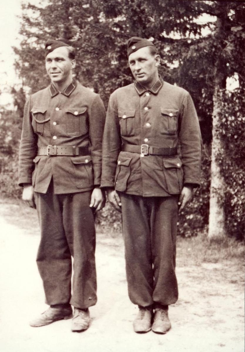Gruppebilde. 2 personer, menn i militæruniform. Utendørs.