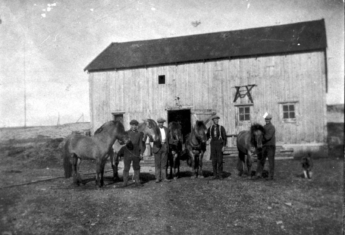 Portrett, flere personer med flere hester foran ei bygning.