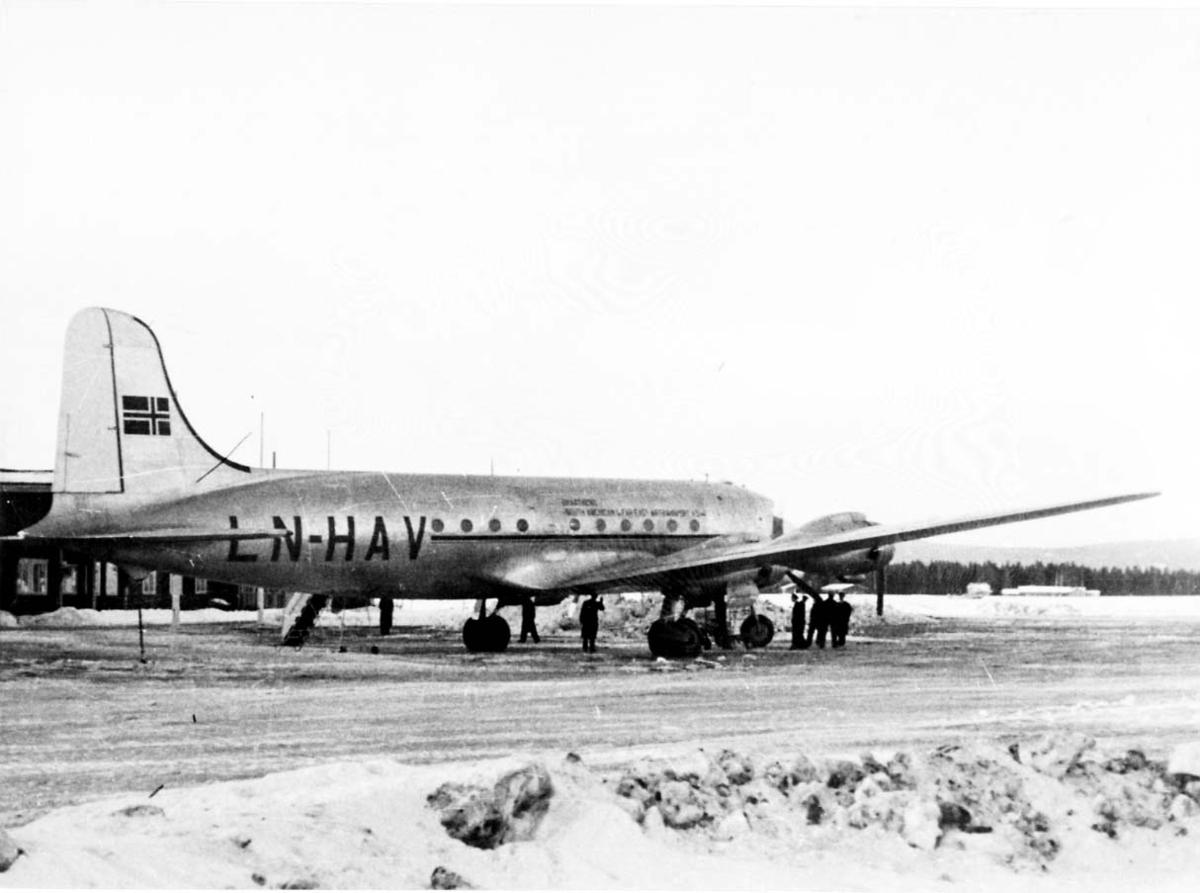 "Lufthavn. 1 fly på bakken, Douglas DC-4 C-54A-5 ldb nr159 Skymaster LN-HAV ""Norse Explorer"" fra Braathens SAFE. Noen personer ved flyet."