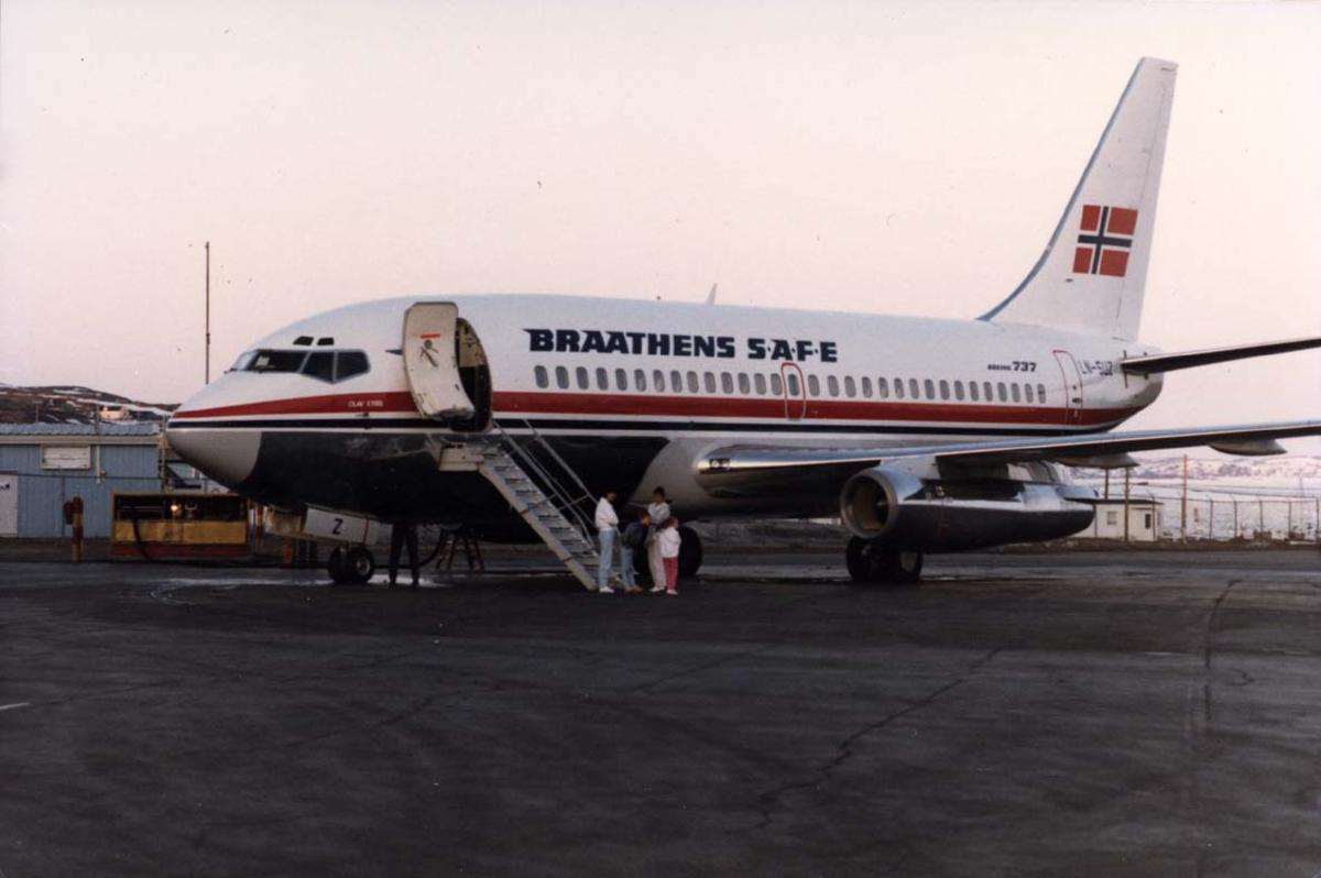 """Lufthavn, 1 fly på bakken, 1 Boeing 737-205 LN-SUZ """"Olav Kyrre"""" fra Braathens SAFE. Noen personer ved flyet."""