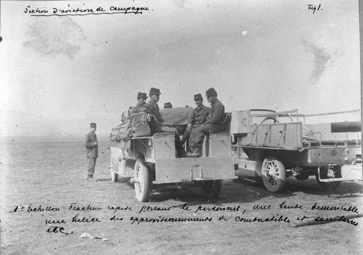 To kjøretøyer - små lastebiler. Noen personer, menn i militæruniform, i det ene kjøretøyet.