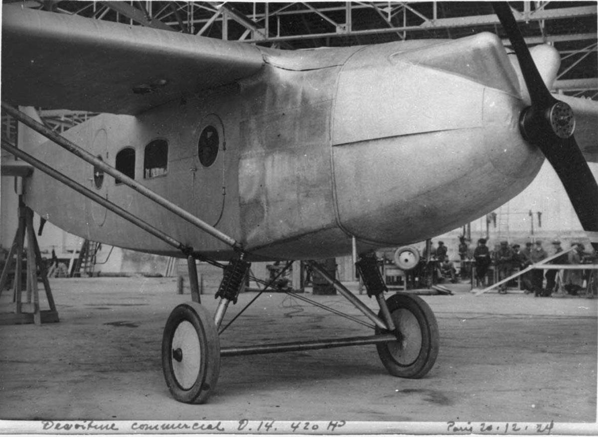 Ett fly inne i hangar, Dewoitine D14. Flere prsoner i bakgrunnen.