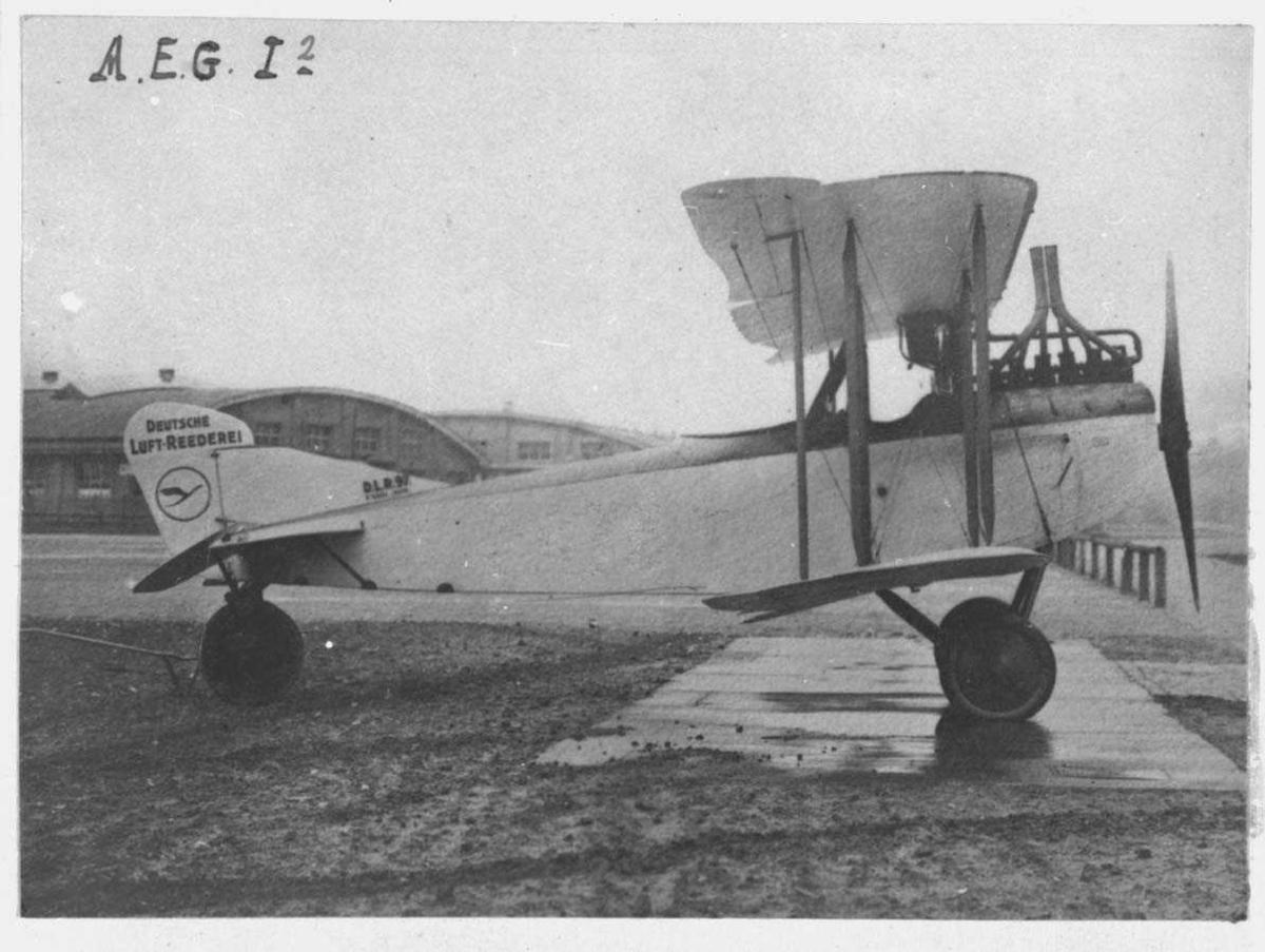 Ett fly på bakken. A.E.G. C I. Hangarer i bakgrunn
