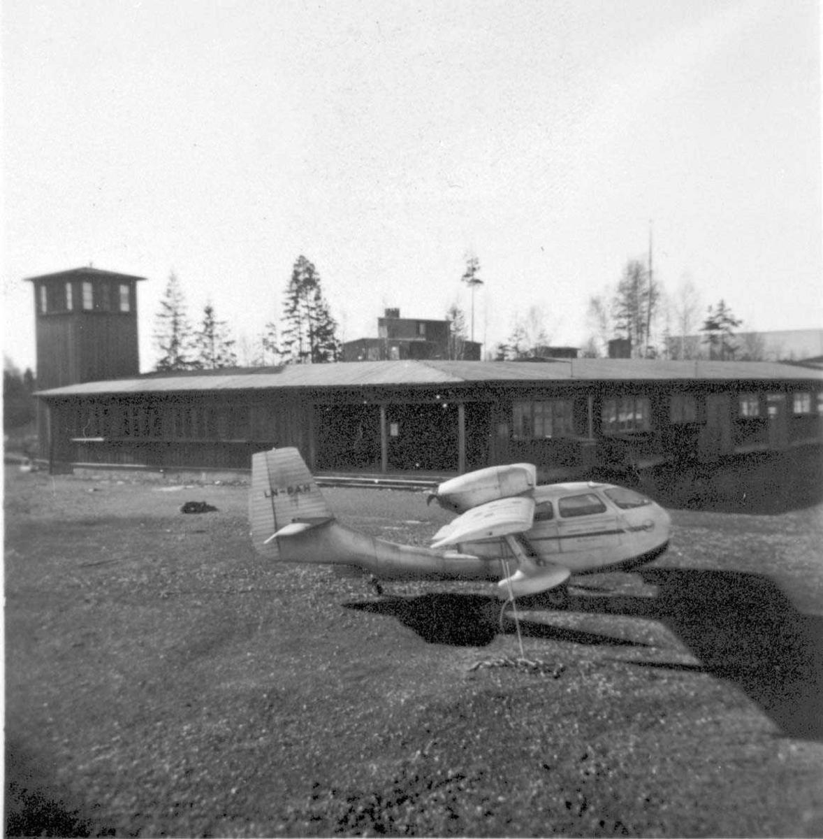 Lufthavn. Ett fly på bakken, Republic RC-3 Seabee LN-PAH fra Widerøes Flyveselskap A/S. Kontrolltårnet i bakgrunnen