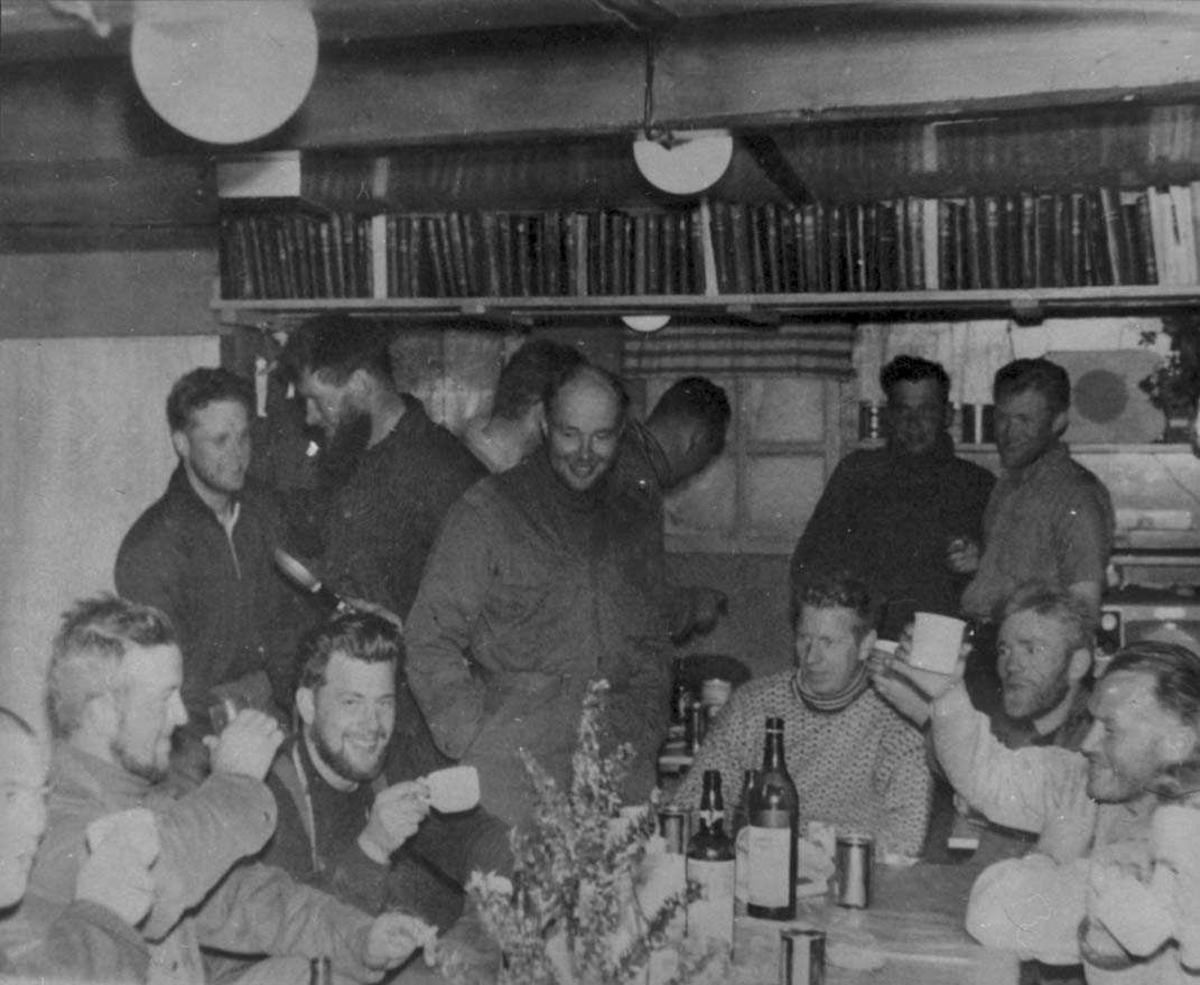 Sosial sammenkomsrt. Mange personer samlet inne i ei bygning rundt et dekket bord.