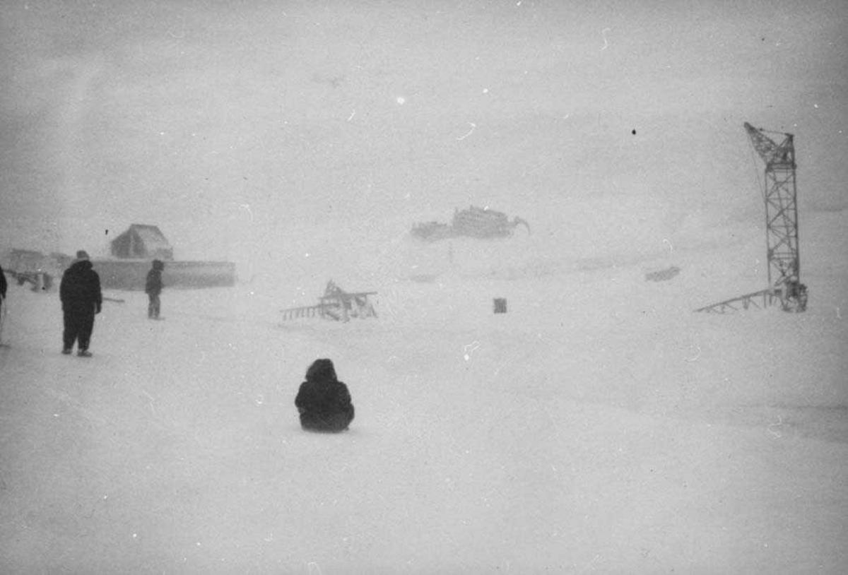 Noen personer ute i snøstorm. Utstyr, kjøretøy og heisekran i bakgrunnen.