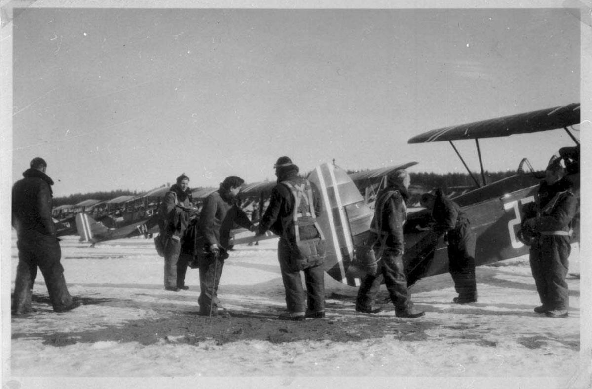 Lufthavn. Flere fly på bakken, Fokker C.V.E. med skiunderstell. Noen personer ved flyene. Snø på bakken.