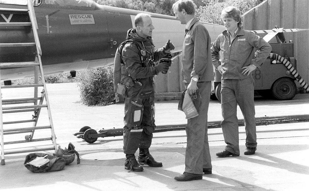 3 personer snakker sammen ved siden av et fly.