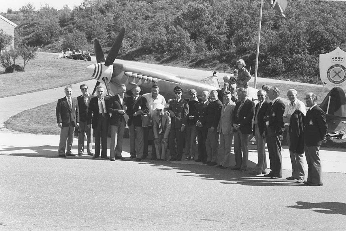 Mange personer samlet foran et eldre jagerfly.