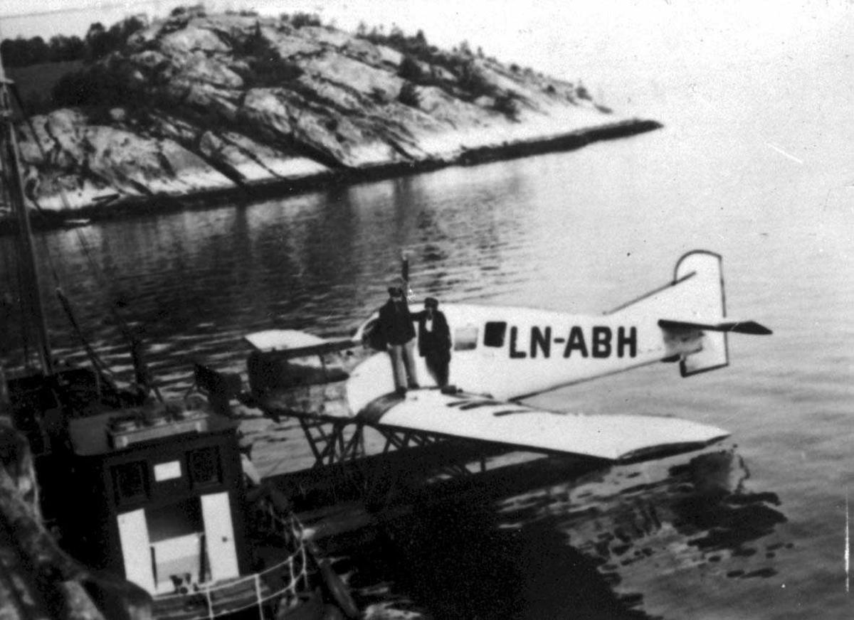 Ett fly Junkers F.13W. I 1932 omregistrert til LN - ABH og solgt til Nord-Norges Aero A/S, Narvik. Det står to personer på vingen av flyet. En mann og en kvinne.