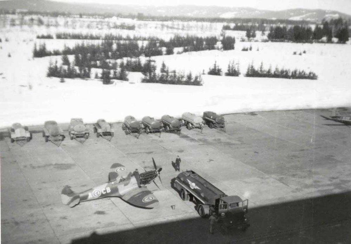 1 fly på bakken. Spitfire. 1 tankbil og 2 personer ved Spitfiren. Flere tankvonger i bakgrunnen.