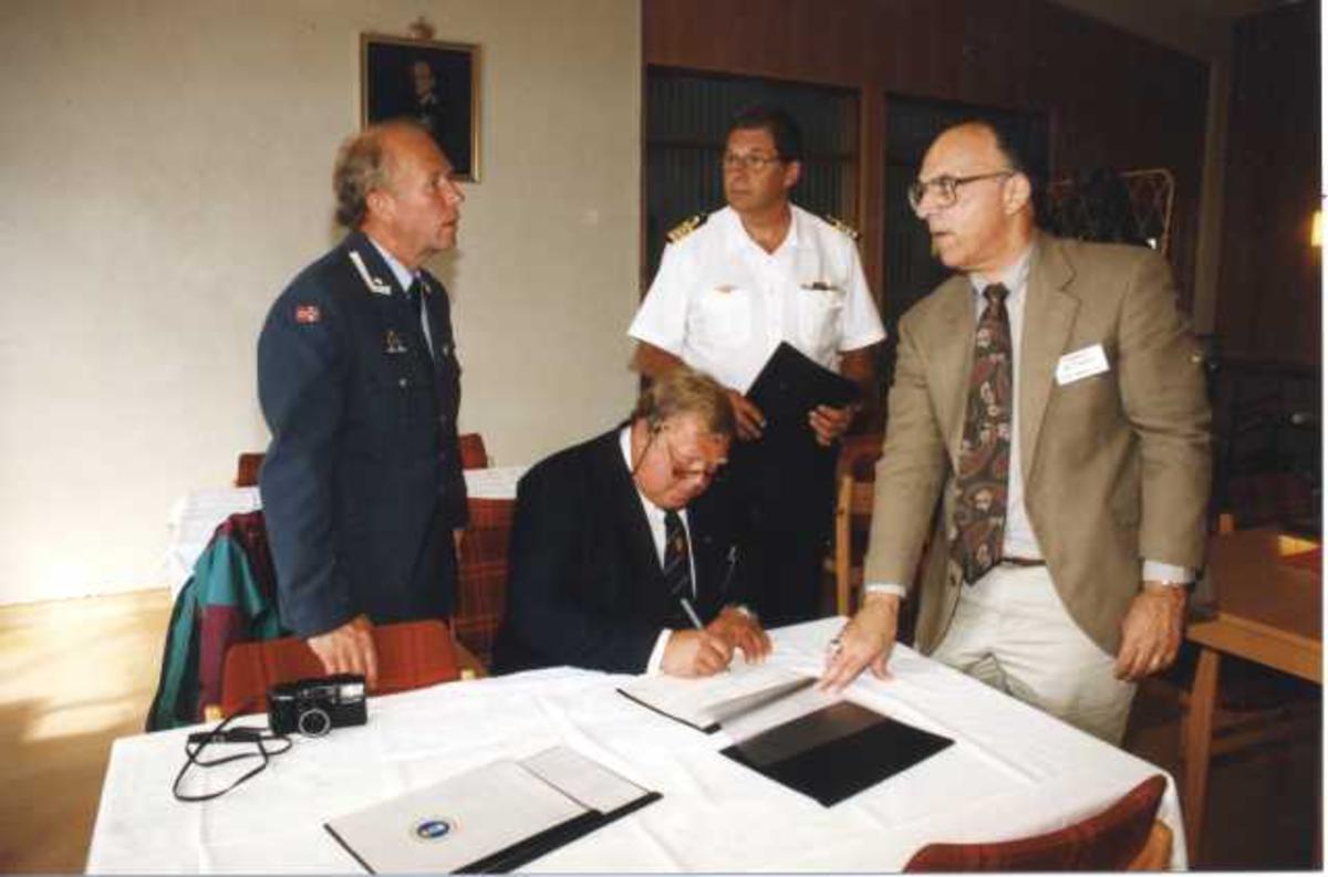 Fire personer, menn, noen i militæruniform. Underskriving av kontrakt/avtale eller lignende.
