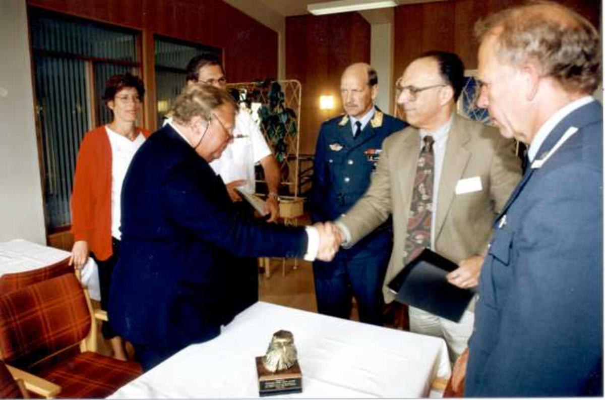 Seks personer ved et bord, en kvinne og 5 menn. Noen i militæruniform. Undertegning av kontrakt/avtale.