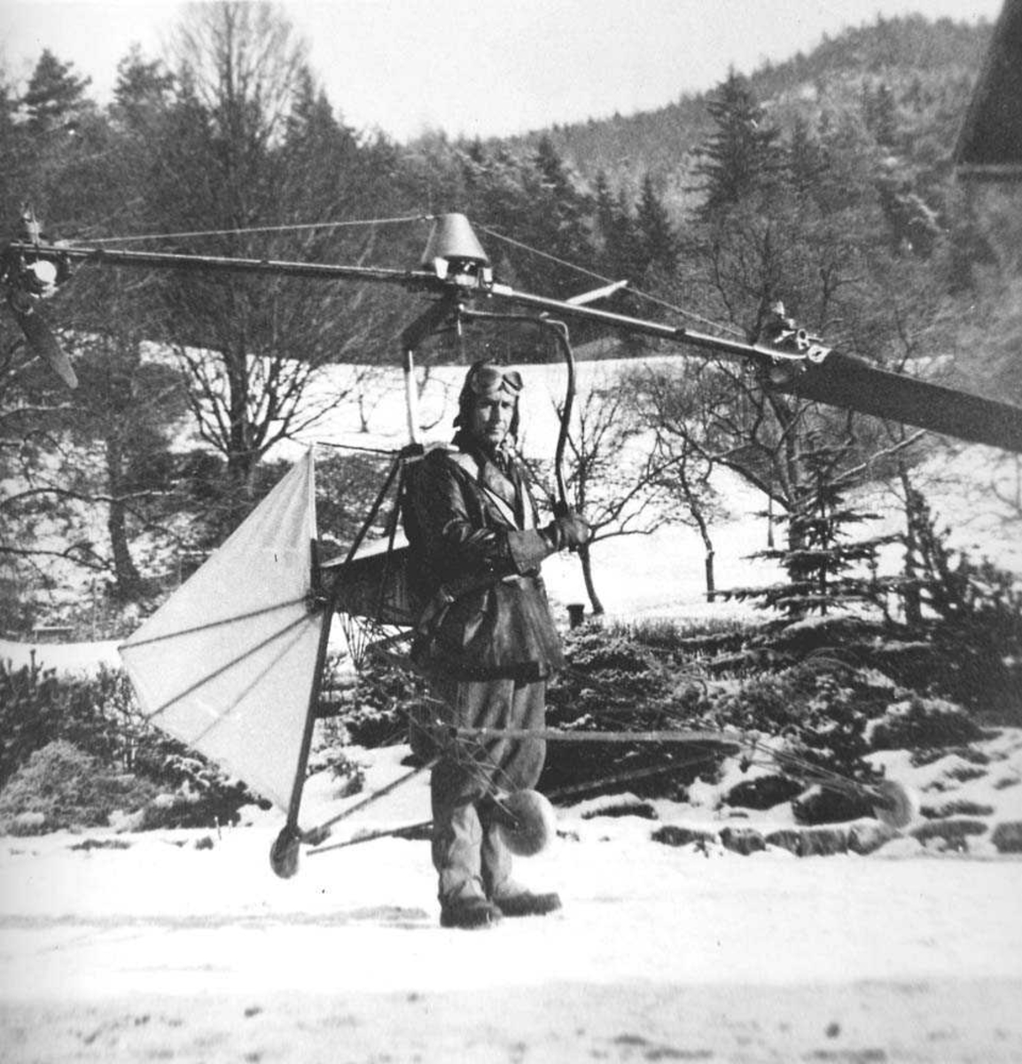 1 person som står med et helikopter på ryggen. Skog i bakgrunnen.
