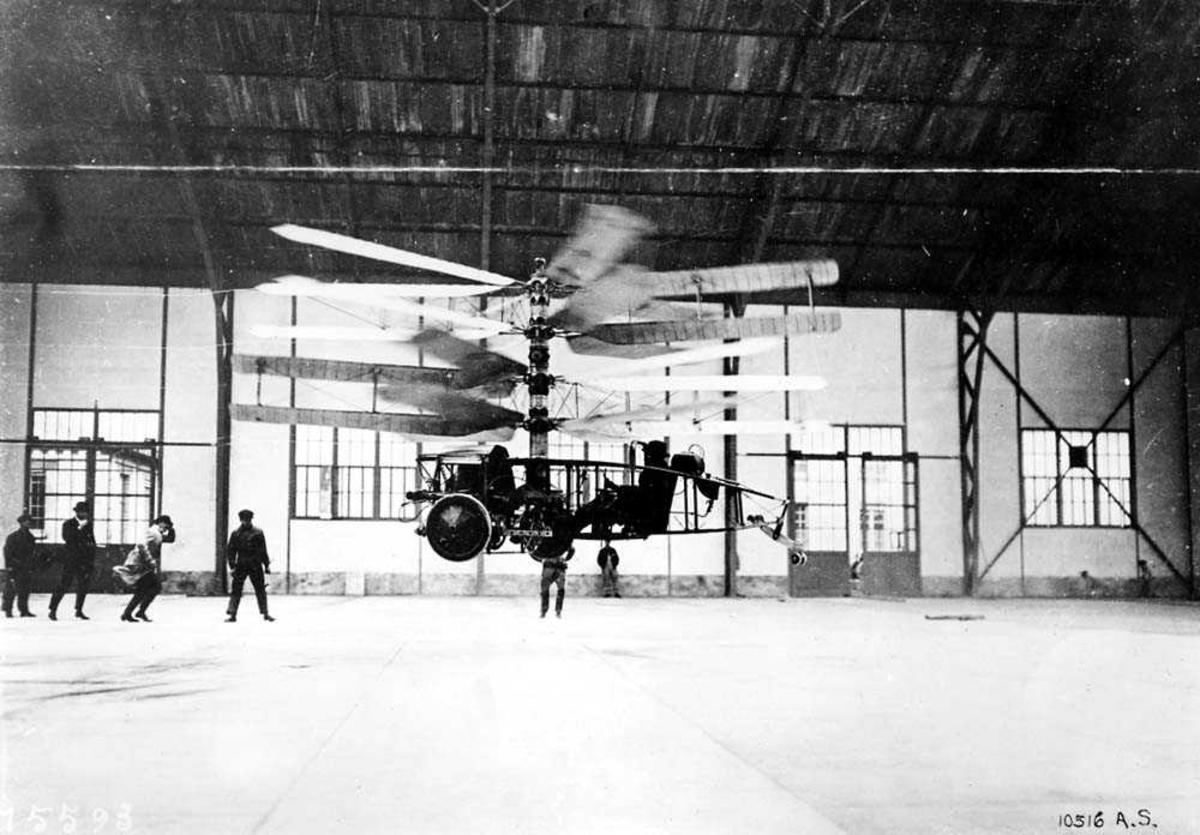 1 helikopter i luften inne i en hangar. Flere personer i hangaren.