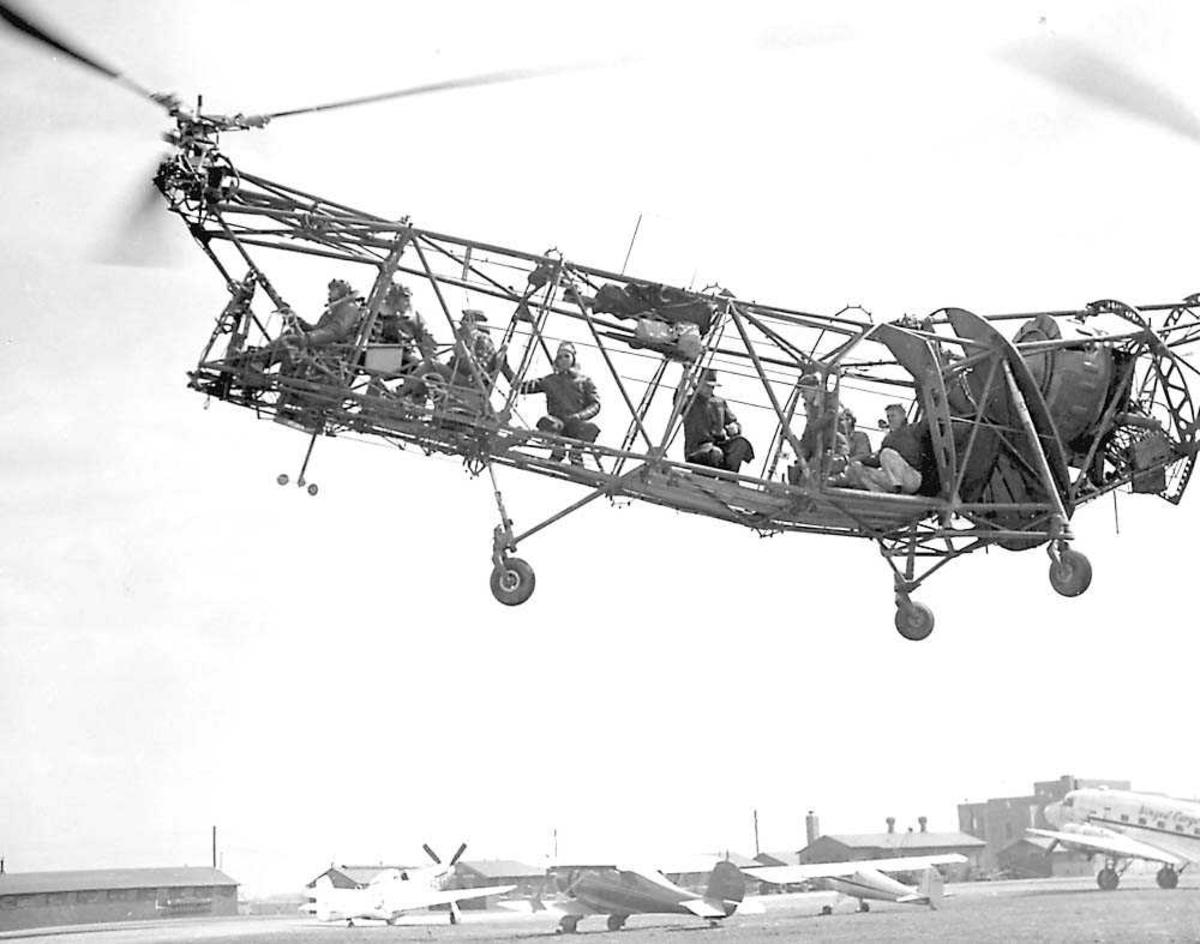 1 helikopter i luften. Piasecki PV-3 (HP-1). Flere personer i helikoptret. Flere fly på bakken.