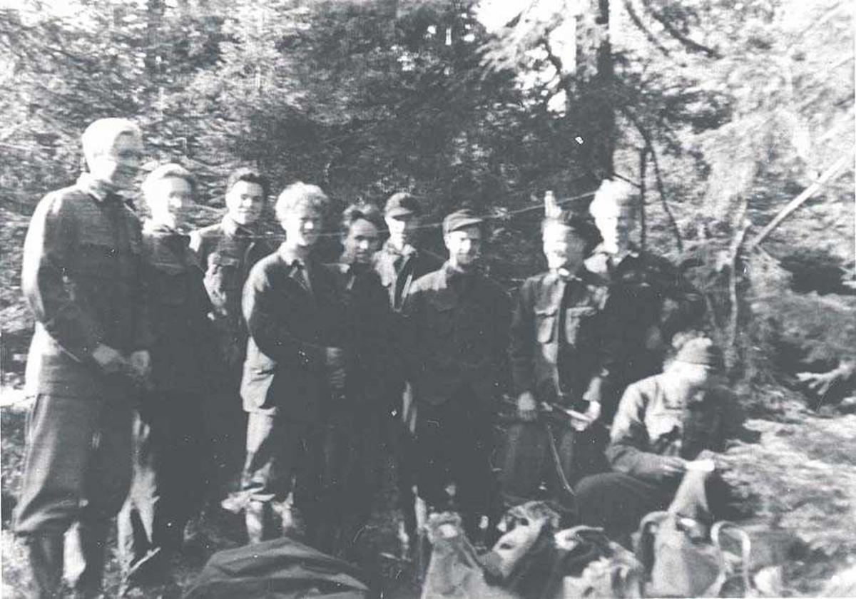 Flere personer i skogen. Menn i uniform.